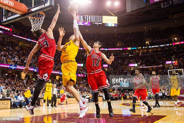 Joakim Noah and Kirk Hinrich of the Chicago Bulls try to stop Timofey Mozgov of the Cleveland Cavaliers in the first half during Game Five in the...
