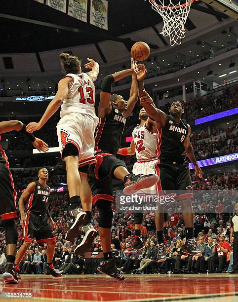 Joakim Noah and Taj Gibson of the Chicago Bulls battle for a rebound with Chris Bosh and LeBron James of the Miami Heat in Game Three of the Eastern...
