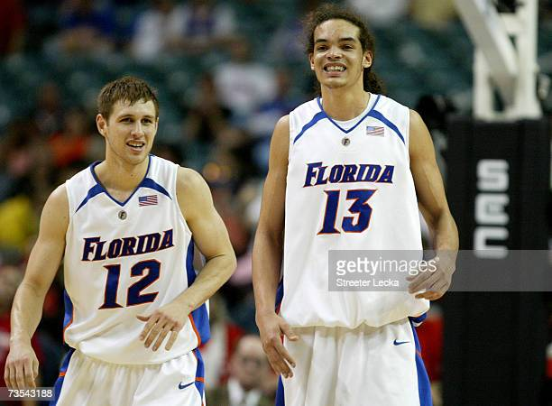 Joakim Noah and teammate Lee Humphrey of the Florida Gators laugh after Noah shot an airball during their semifinal game victory over the Ole Miss...