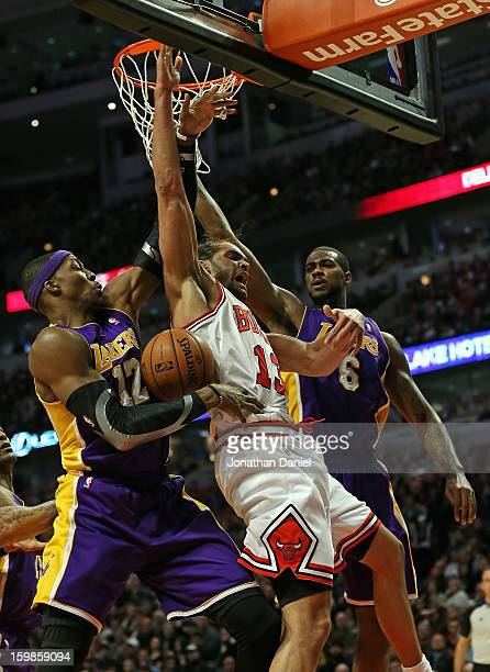 Joakim Noah of the Chicago Bulls battles for a rebound with Dwight Howard and Earl Clark of the Los Angeles Lakers at the United Center on January 21...