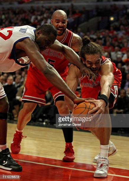 Joakim Noah of the Chicago Bulls battles for the ball with Elton Brand of the Philadelphia 76ers in front of Carlos Boozer at the United Center on...