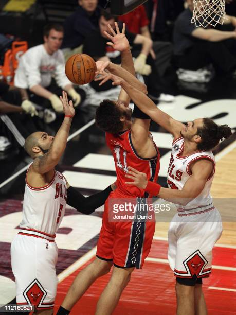Joakim Noah of the Chicago Bulls blocks a shot by Brook Lopez of the New Jersey Nets as Carlos Boozer reaches for the ball at United Center on April...