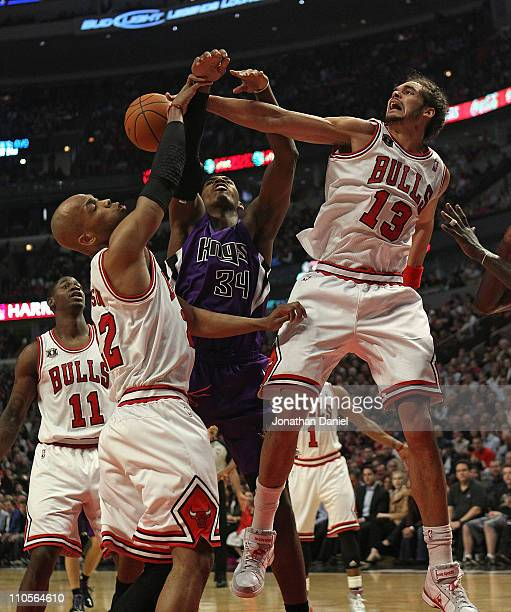 Joakim Noah of the Chicago Bulls blocks a shot by Jason Thompson of the Sacramento Kings as teammate Taj Gibson also defends at the United Center on...