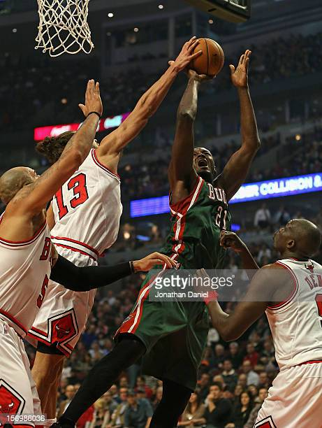 Joakim Noah of the Chicago Bulls blocks a shot by Samuel Dalembert of the Milwaukee Bucks as he tries to shoot over Loul Deng and Carlos Boozer at...