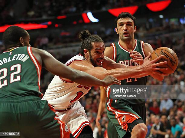 Joakim Noah of the Chicago Bulls drives between Khris Middleton and Zaza Pachulia of the Milwaukee Bucks during the first round of the 2015 NBA...