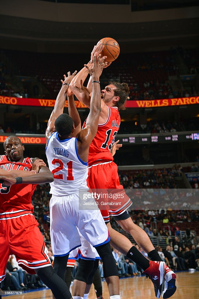 Joakim Noah #13 of the Chicago Bulls drives to the basket ;against Thaddeus Young #21 of the Philadelphia 76ers on December 12, 2012 at the Wells Fargo Center in Philadelphia, Pennsylvania.