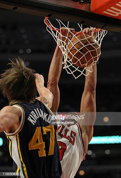 Joakim Noah of the Chicago Bulls dunks the ball against Andrei Kirilenko of the Utah Jazz at the United Center on March 12 2011 in Chicago Illinois...