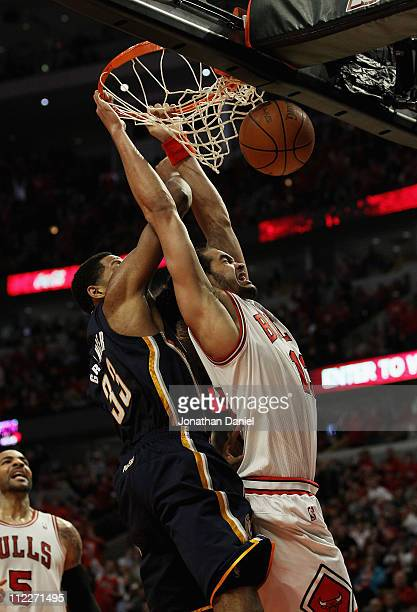 Joakim Noah of the Chicago Bulls dunks the ball and is fouled by Danny Granger of the Indiana Pacers in Game One of the Eastern Conference...
