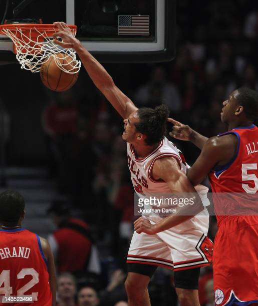Joakim Noah of the Chicago Bulls dunks the ball over Elton Brand and Lavoy Allen of the Philadelphia 76ers in Game One of the Eastern Conference...