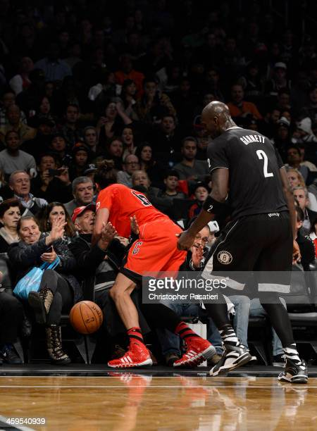 Joakim Noah of the Chicago Bulls falls onto and unidentified fan during the second quarter against the Brooklyn Nets at the Barclays Center on...