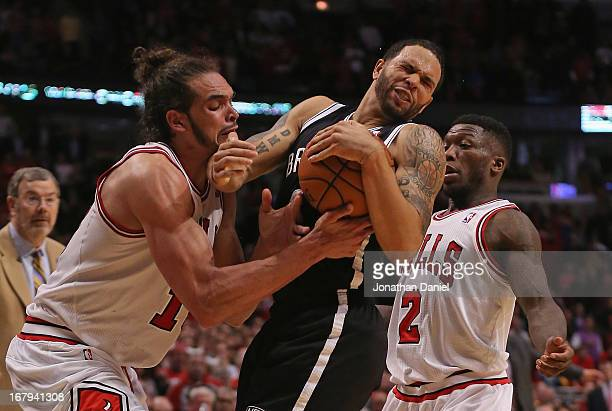 Joakim Noah of the Chicago Bulls forces a jump ball with Deron Williams of the Brooklyn Nets next to Nate Robinson in Game Six of the Eastern...