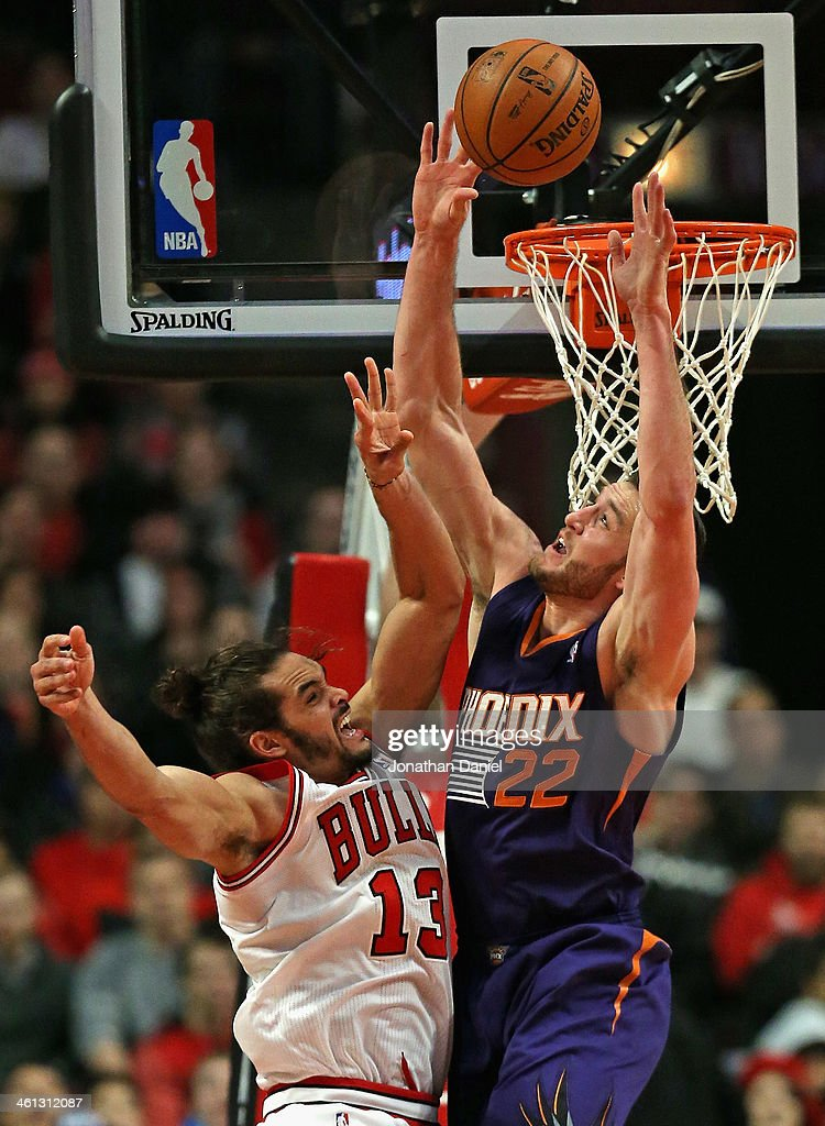 Joakim Noah #13 of the Chicago Bulls gets off a shot under pressure from Miles Plumlee #22 of the Phoenix Suns at the United Center on January 7, 2014 in Chicago, Illinois.