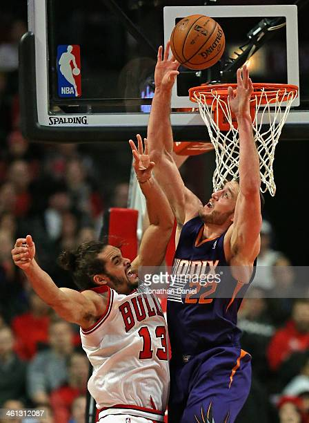 Joakim Noah of the Chicago Bulls gets off a shot under pressure from Miles Plumlee of the Phoenix Suns at the United Center on January 7 2014 in...