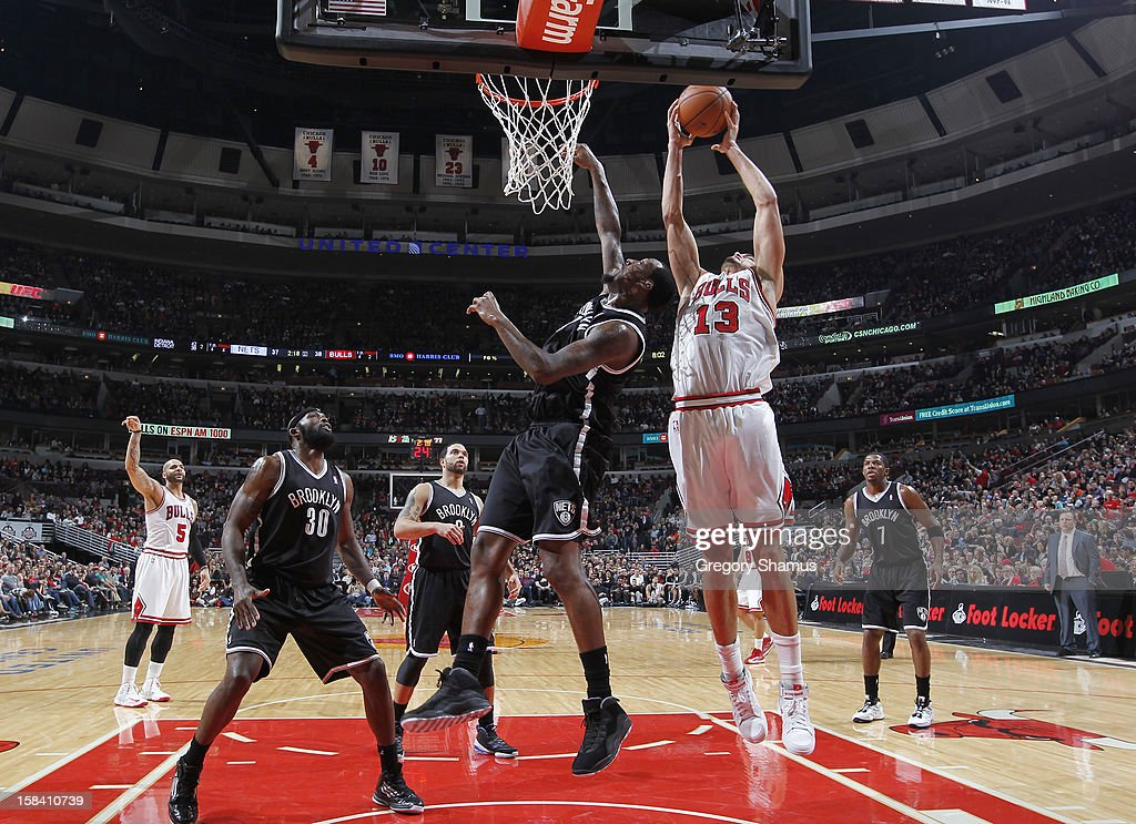 Joakim Noah #13 of the Chicago Bulls goes to the basket against Andray Blatche #0 of the Brooklyn Nets on December 15, 2012 at the United Center in Chicago, Illinois.