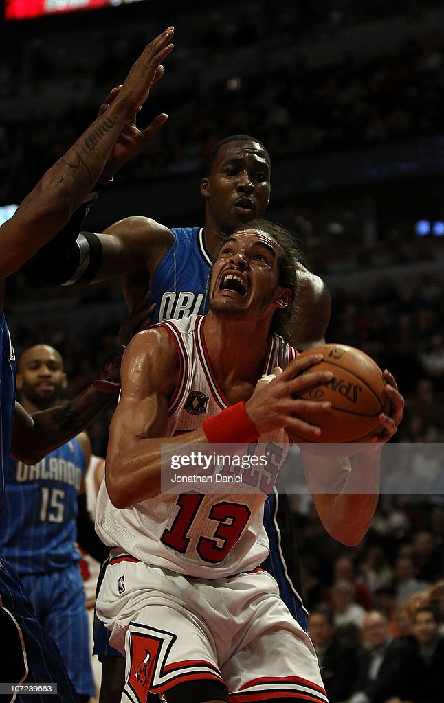 Joakim Noah #13 of the Chicago Bulls goes up for a shot against Dwight Howard #12 of the Orlando Magic at the United Center on December 1, 2010 in Chicago, Illinois. The Magic defeated the Bulls 107-78.