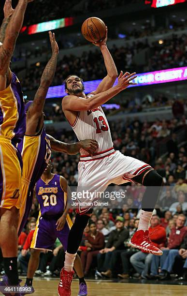 Joakim Noah of the Chicago Bulls goes up for a shot against Robert Sacre and Jordan Hill of the Los Angeles Lakers at the United Center on January 20...