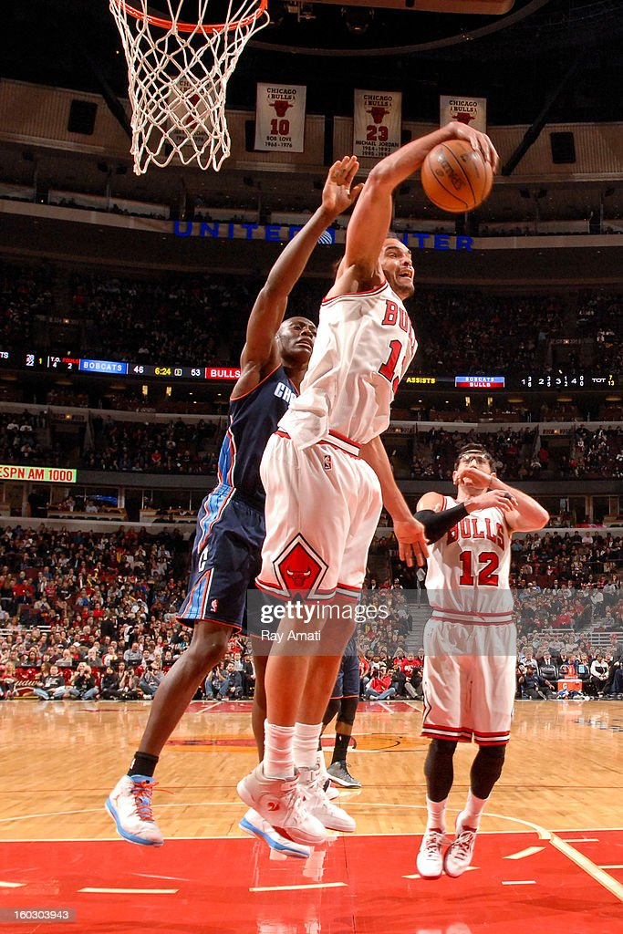 Joakim Noah #13 of the Chicago Bulls grabs a rebound against Bismack Biyombo #0 of the Charlotte Bobcats on January 28, 2013 at the United Center in Chicago, Illinois.