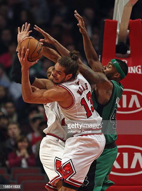 Joakim Noah of the Chicago Bulls grabs a rebound away from Chris Wilcox of the Boston Celtics and teammate Taj Gibson at the United Center on...