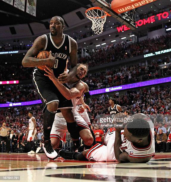 Joakim Noah of the Chicago Bulls grabs Andray Blatche of the Brooklyn Nets as Nate Robinson hits the floor in Game Six of the Eastern Conference...