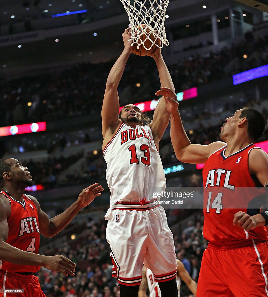 Joakim Noah #13 of the Chicago Bulls grabs one of 16 rebounds between Paul Millsap #4 and Gustavo Ayon #14 of the Atlanta Hawks at the United Center on February 11, 2014 in Chicago, Illinois. The Bulls defeated the Hawks 100-85.