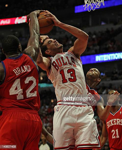 Joakim Noah of the Chicago Bulls is fouled by Evan Turner of the Philadelphia 76ers as Elton Brand gets his hand on the ball in Game One of the...
