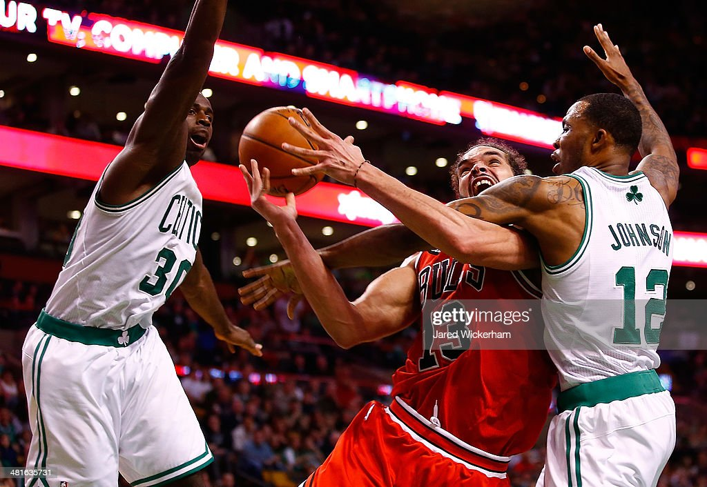 Joakim Noah #13 of the Chicago Bulls is fouled on his way to the basket by Chris Johnson #12 of the Boston Celtics in the second half during the game at TD Garden on March 30, 2014 in Boston, Massachusetts.