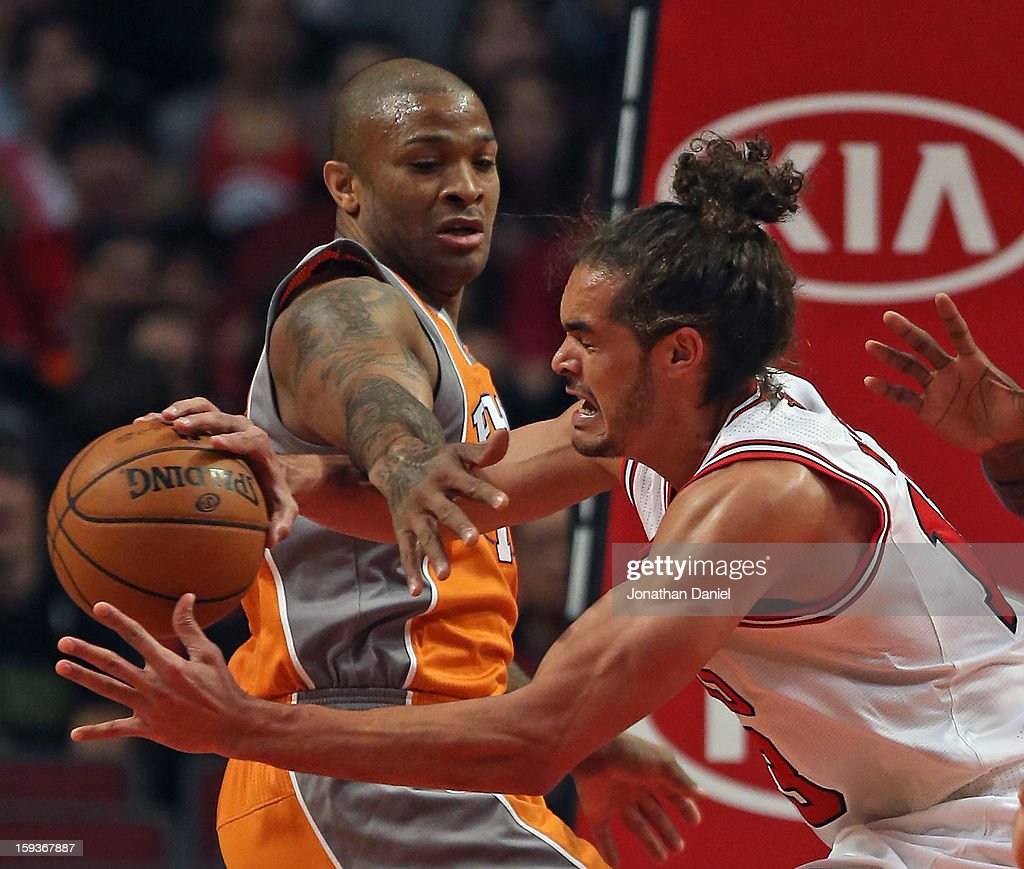 Joakim Noah #13 of the Chicago Bulls is fouled while rebounding by P.J. Tucker #17 of the Phoenix Suns at the United Center on January 12, 2013 in Chicago, Illinois.