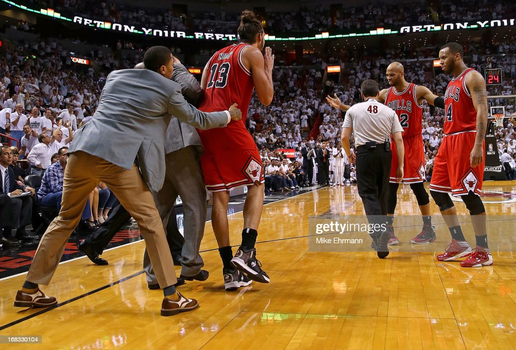 Joakim Noah #13 of the Chicago Bulls is is held back by Derrick Rose after being ejected for arguing with referee Scott Foster #48 during Game Two of the Eastern Conference Semifinals of the 2013 NBA Playoffs against the Miami Heat at American Airlines Arena on May 8, 2013 in Miami, Florida.