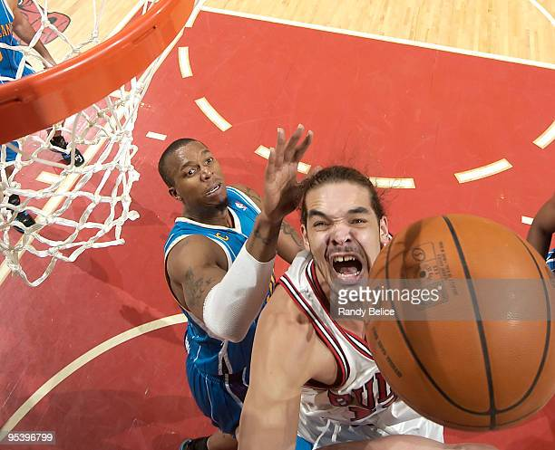 Joakim Noah of the Chicago Bulls jumps towards the ball as Julian Wright of the New Orleans Hornets comes up from behind during the NBA game on...