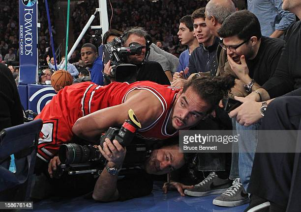 Joakim Noah of the Chicago Bulls lands on a TV camerman as actor Jerry Ferrera of Entourage looks on during the second quarter against the New York...