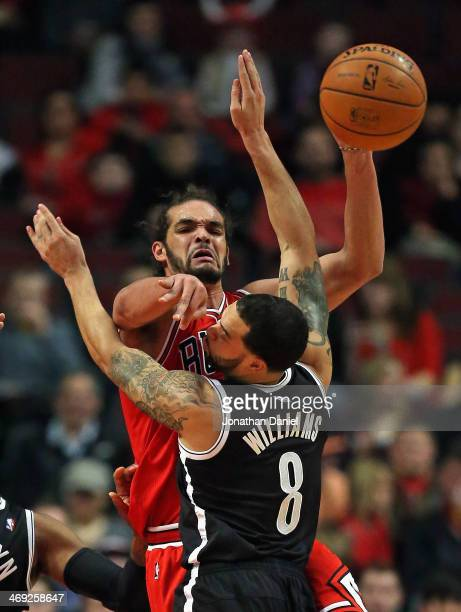 Joakim Noah of the Chicago Bulls passes over Deron Williams of the Brooklyn Nets at the United Center on February 13 2014 in Chicago Illinois NOTE TO...