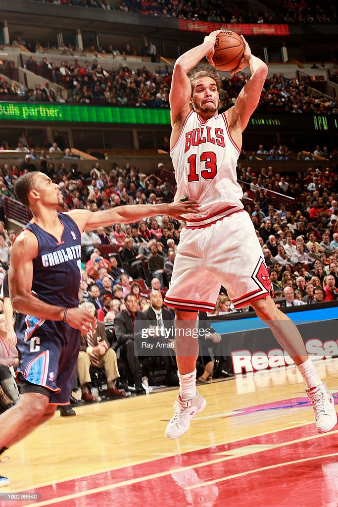Joakim Noah #13 of the Chicago Bulls passes the ball against Ramon Sessions #7 of the Charlotte Bobcats on January 28, 2013 at the United Center in Chicago, Illinois.