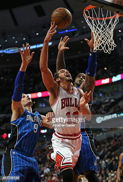 Joakim Noah #13 of the Chicago Bulls puts up a shot between Nikola Vucevic #9 and Glen Davis #11 of the Orlando Magic at the United Center on December 16, 2013 in Chicago, Illinois. The Magic defeated the Bulls 83-82.