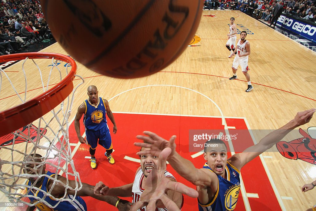 Joakim Noah #13 of the Chicago Bulls reaches for a rebound against (L-R) Carl Landry #7 and Stephen Curry #30 of the Golden State Warriors on January 25, 2012 at the United Center in Chicago, Illinois.