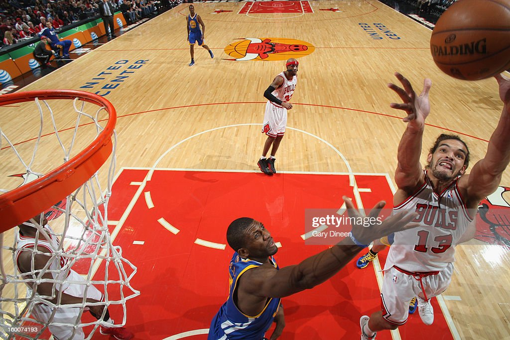 Joakim Noah #13 of the Chicago Bulls reaches for a rebound against Festus Ezeli #31 of the Golden State Warriors on January 25, 2012 at the United Center in Chicago, Illinois.