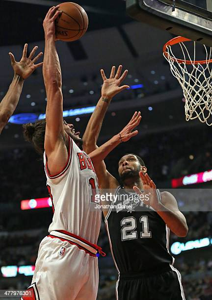 Joakim Noah of the Chicago Bulls shoots against Tim Duncan of the San Antonio Spurs at the United Center on March 11 2014 in Chicago Illinois NOTE TO...