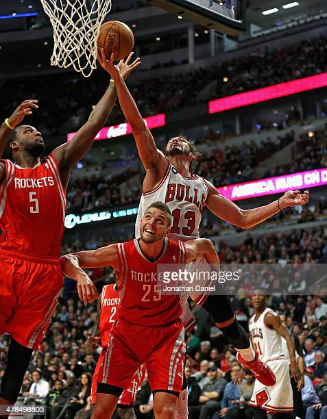 Joakim Noah of the Chicago Bulls shoots over Chander Parsons and Jordan Hamilton of the Houston Rockets at the United Center on March 13 2014 in...