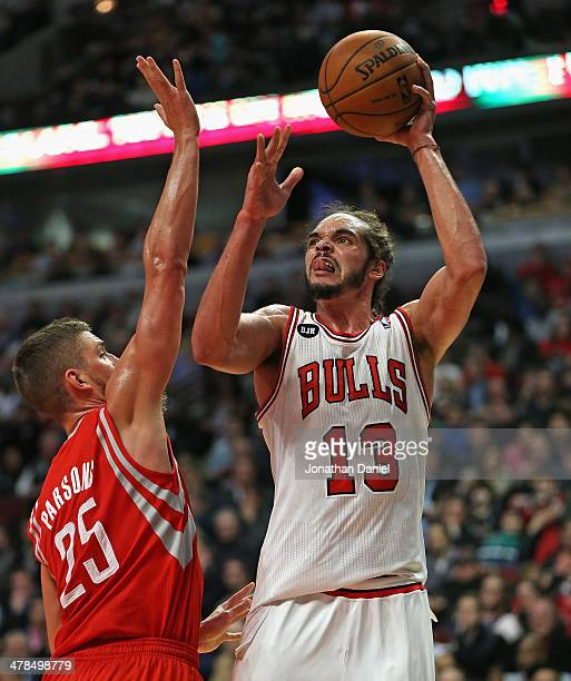 Joakim Noah of the Chicago Bulls shoots over Chandlker Parsons of the Houston Rockets at the United Center on March 13 2014 in Chicago Illinois The...