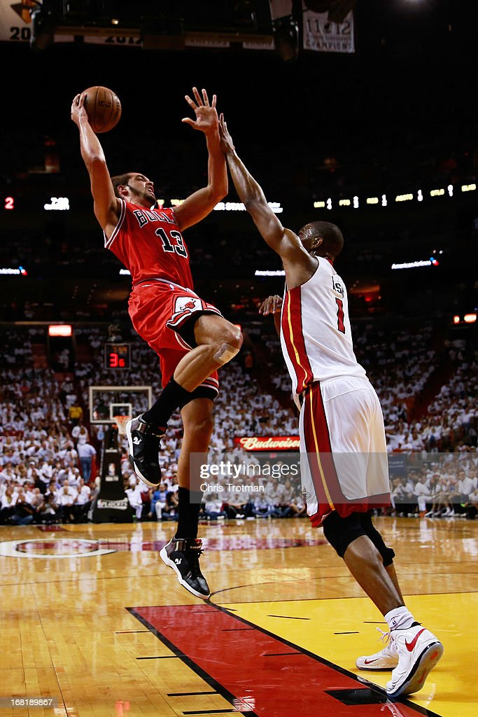 Joakim Noah #13 of the Chicago Bulls shoots over Chris Bosh #1 of the Miami Heat during Game One of the Eastern Conference Semifinals of the 2013 NBA Playoffs at American Airlines Arena on May 6, 2013 in Miami, Florida.