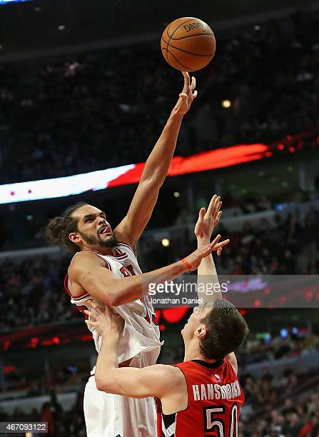 Joakim Noah of the Chicago Bulls shoots over Tyler Hansbrough of the Toronto Raptors at the United Center on March 20 2015 in Chicago Illinois The...