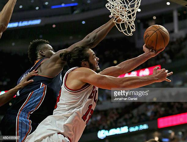 Joakim Noah of the Chicago Bulls shoots under pressure from Jeff Adrien of the Charlotte Bobcats at the United Center on November 18 2013 in Chicago...