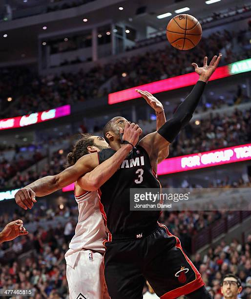 Joakim Noah of the Chicago Bulls wraps up Dwyane Wade of the Miami Heat as he tries to rebound at the United Center on March 9 2014 in Chicago...