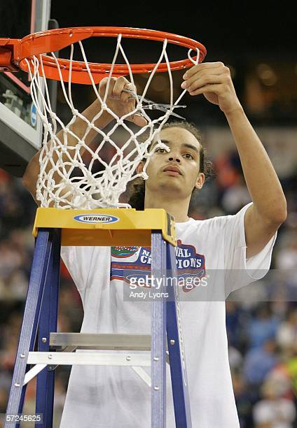 Joakim Noah of the Florida Gators celebrates by cutting down the net after defeating the UCLA Bruins 73-57 during the National Championship game of...