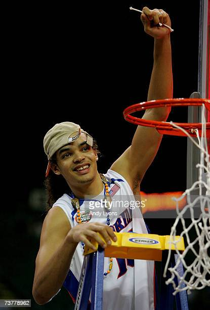 Joakim Noah of the Florida Gators cuts down the net after his team defeated the Ohio State Buckeyes during the NCAA Men's Basketball Championship...