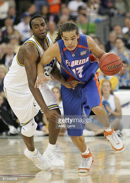 Joakim Noah of the Florida Gators drives around the defense of Luc Richard Mbah a Moute of the UCLA Bruins in the second half during the National...