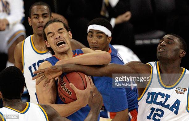 Joakim Noah of the Florida Gators protects the ball from Alfred Aboya of the UCLA Bruins during the National Championship game of the NCAA Men's...