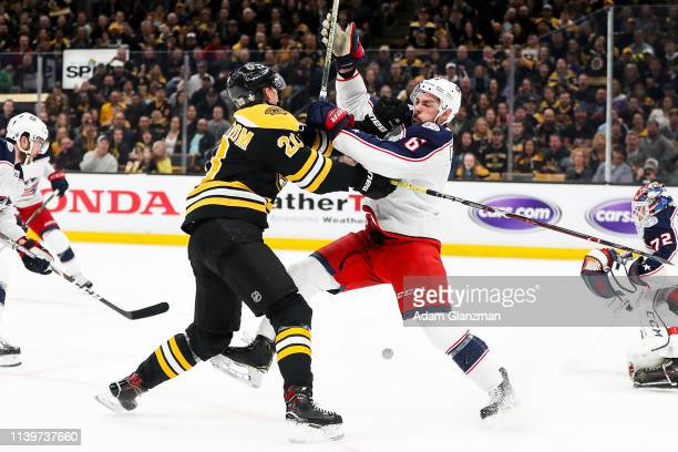 Joakim Nordstrom of the Boston Bruins pushes Adam Clendening of the Columbus Blue Jackets in Game Two of the Eastern Conference Second Round during...