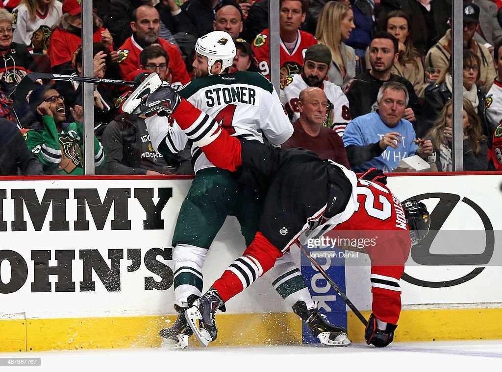 Joakim Nordstrom #42 of the Chicago Blackhawks and Clayton Stoner #4 of the Minnesota Wild collide along the boards in Game One of the Second Round of the 2014 NHL Stanley Cup Playoffs at the United Center on May 2, 2014 in Chicago, Illinois.