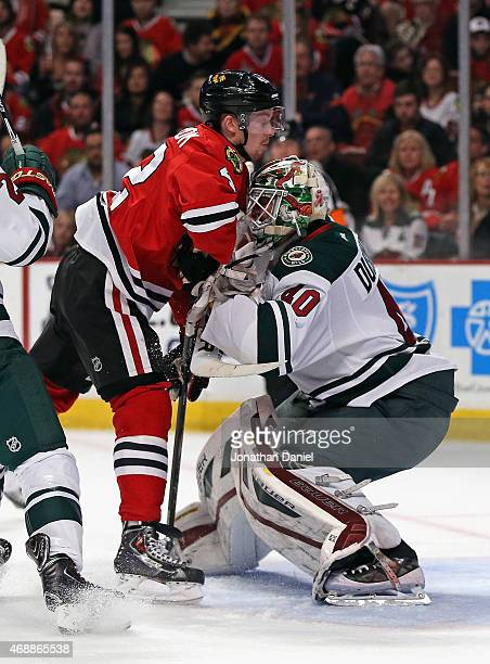 Joakim Nordstrom of the Chicago Blackhawks collides with Devan Dubnyk of the Minnesota Wild at the United Center on April 7 2015 in Chicago Illinois