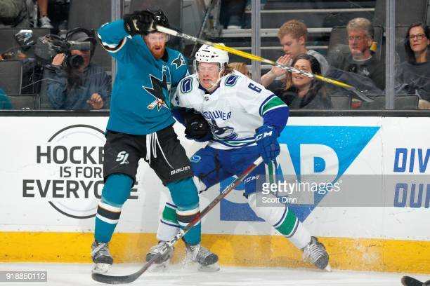 Joakim Ryan of the San Jose Sharks and Brock Boeser of the Vancouver Canucks battle along the boards at SAP Center on February 15 2018 in San Jose...